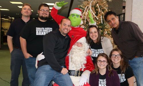 photo of employees posing with Santa at Christmas branch event